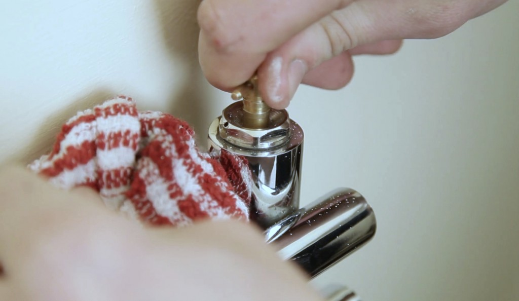 a man turning the bleed nipple of a radiator anticlockwise