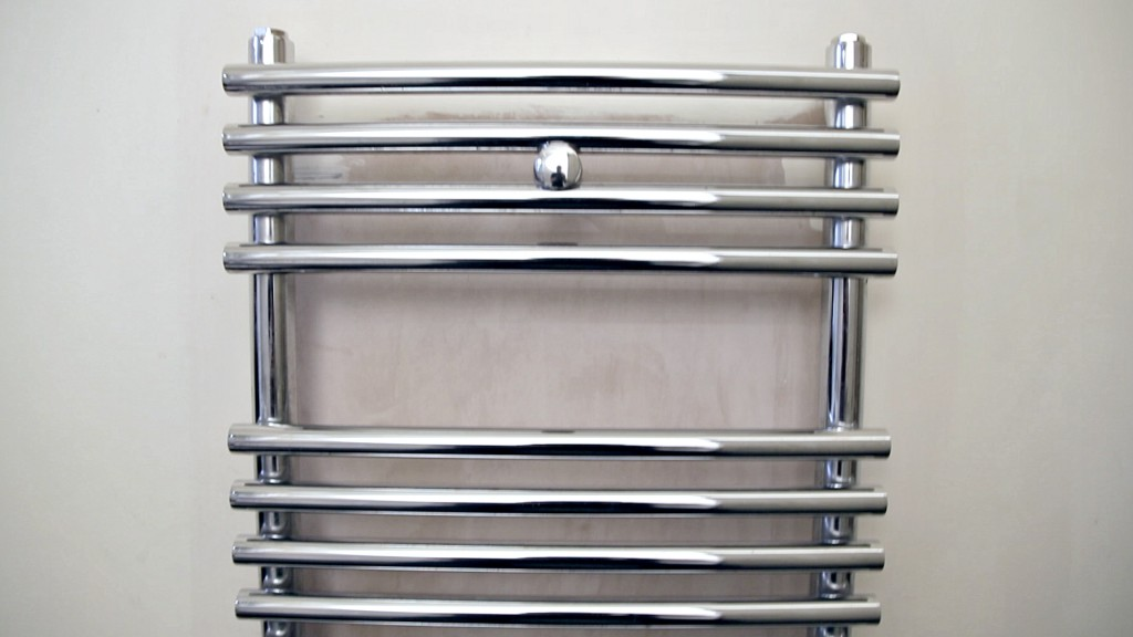 Front on shot of a heated towel rail on a wall in a bathroom