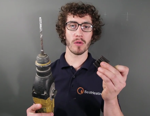 Man with glasses holding a drill and a set of rawlplugs