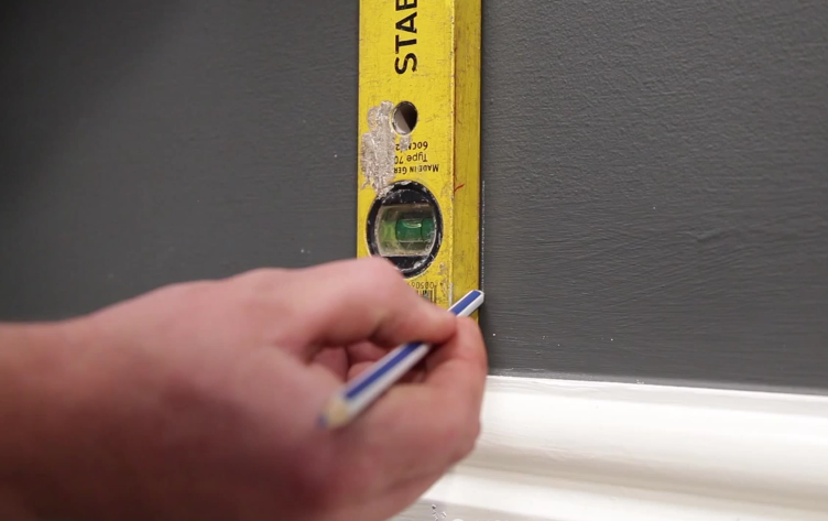 Man using a spirit level and a pencil to mark a line on the wall