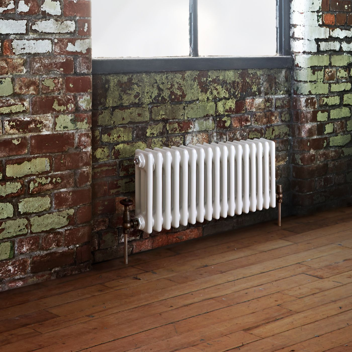 white column radiator under a window on a brick wall