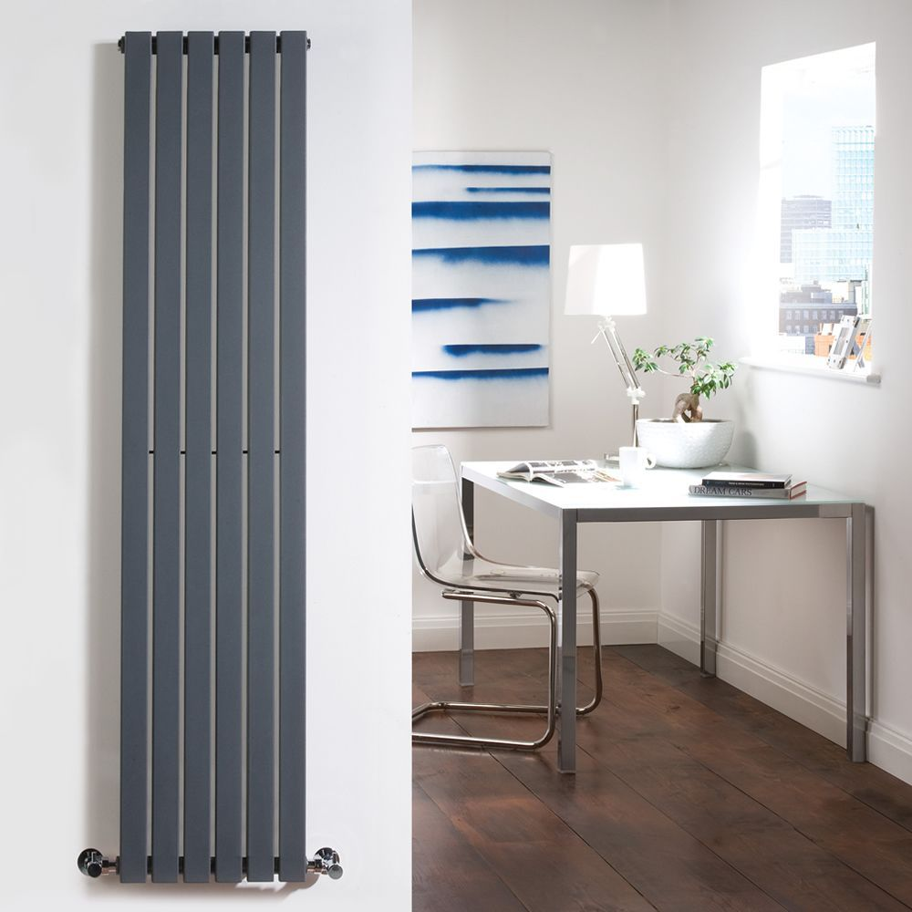 Vertical designer radiator on a wall with a chair and desk in the background