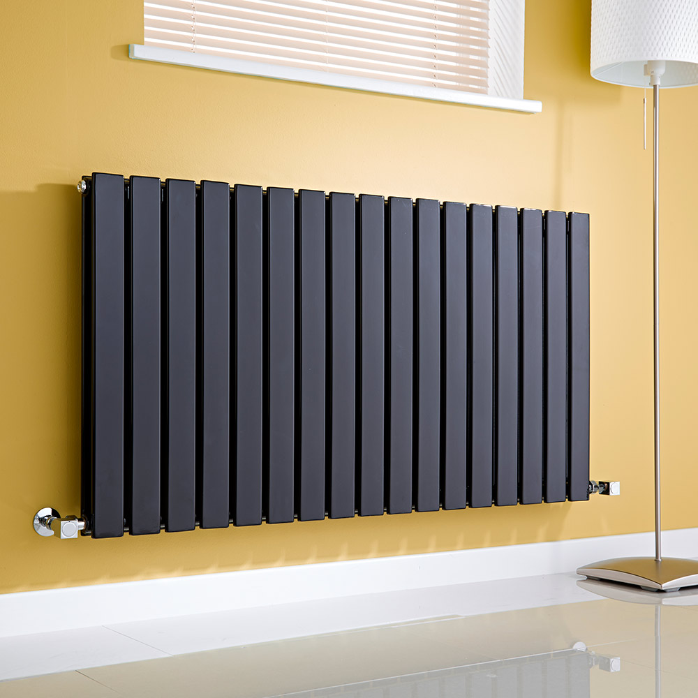 Anthracite Milano Alpha Radiator on a wall in a lounge next to a window and a lamp - changing a radiator