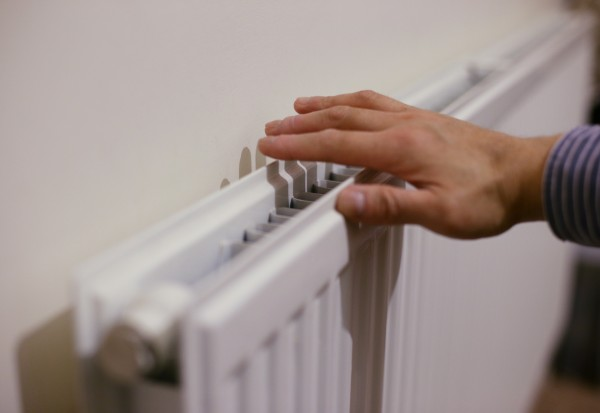 A hand checking the level of heat at the top of a radiator