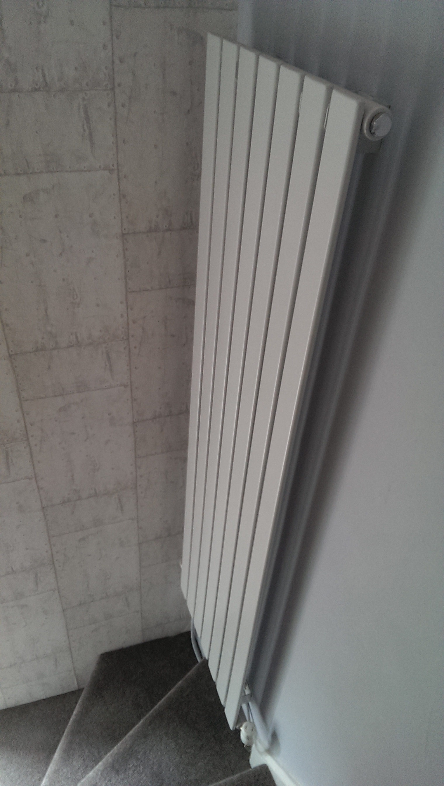 Tall vertical radiator at the bottom of the stairs