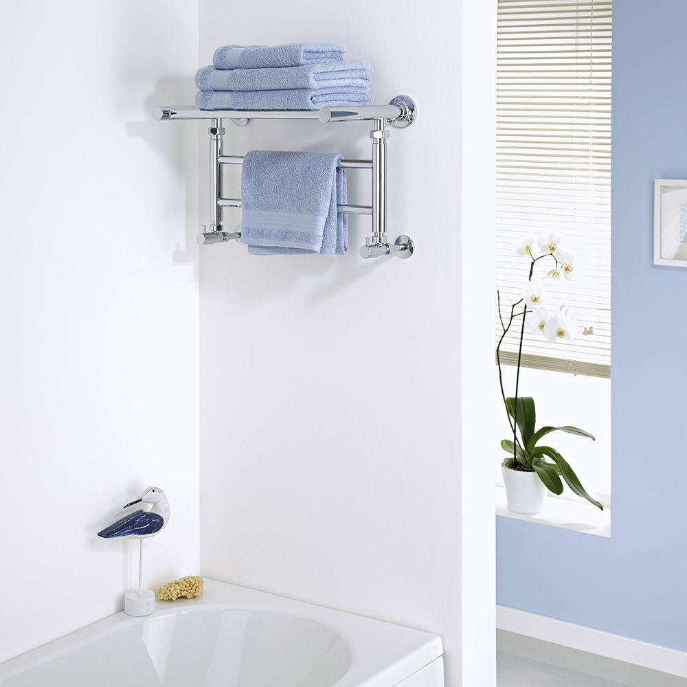 Milano Pendle Chrome Heated Towel Rail with a shelf above a bath in a bathroom
