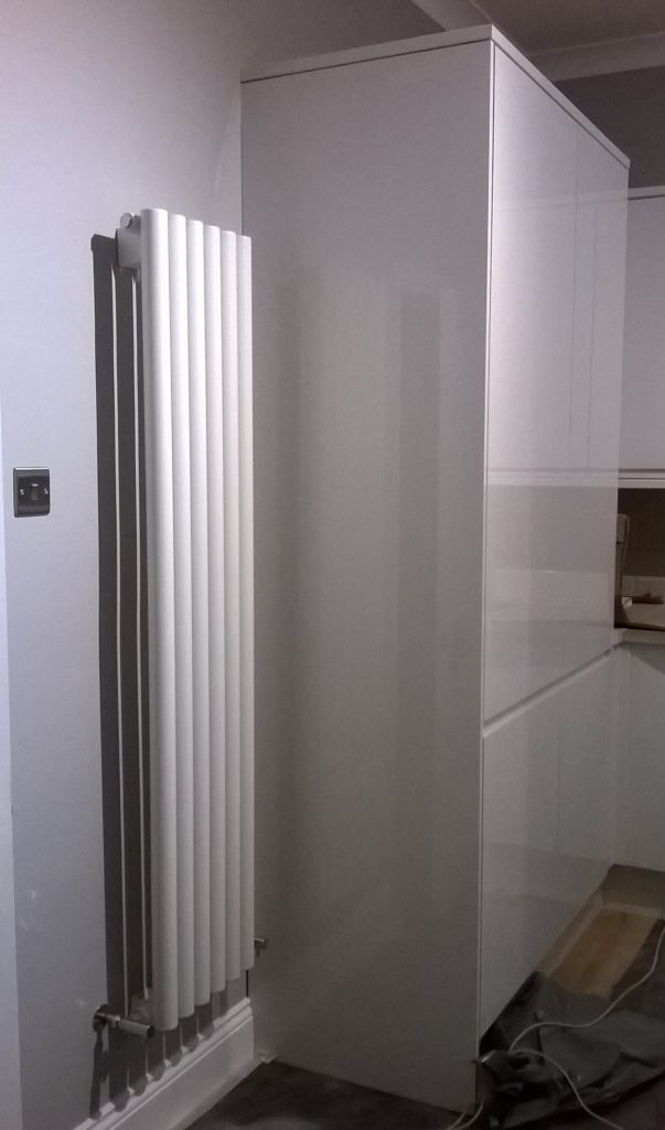 Milano Java white round tubed vertical designer radiator on a kitchen wall