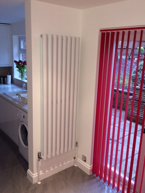 White diamond panel radiator on a kitchen wall with a red net curtain next to it