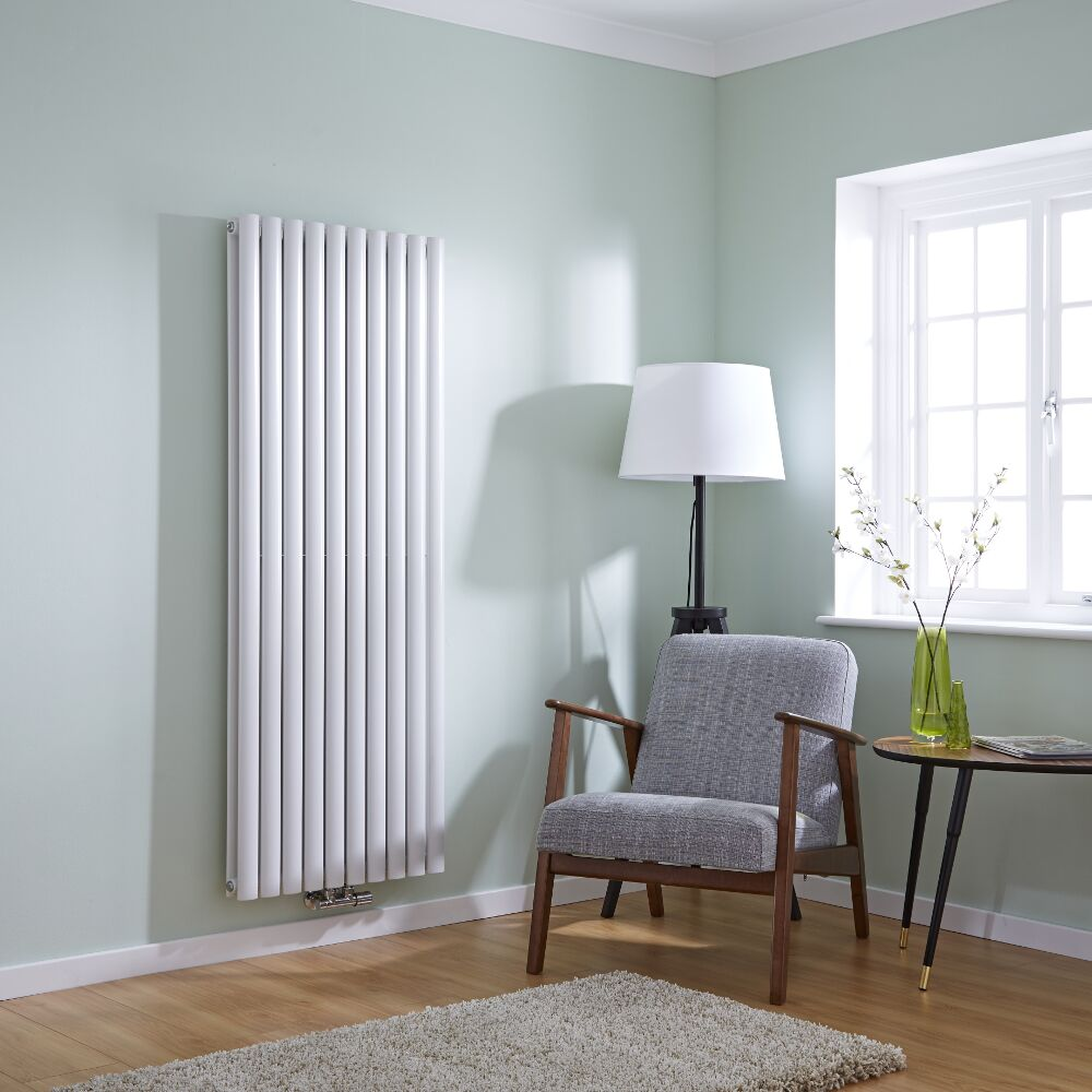 Tall white milano aruba flow central connection radiator on a wall in a room with a chair and a rug on a bare wooden floor