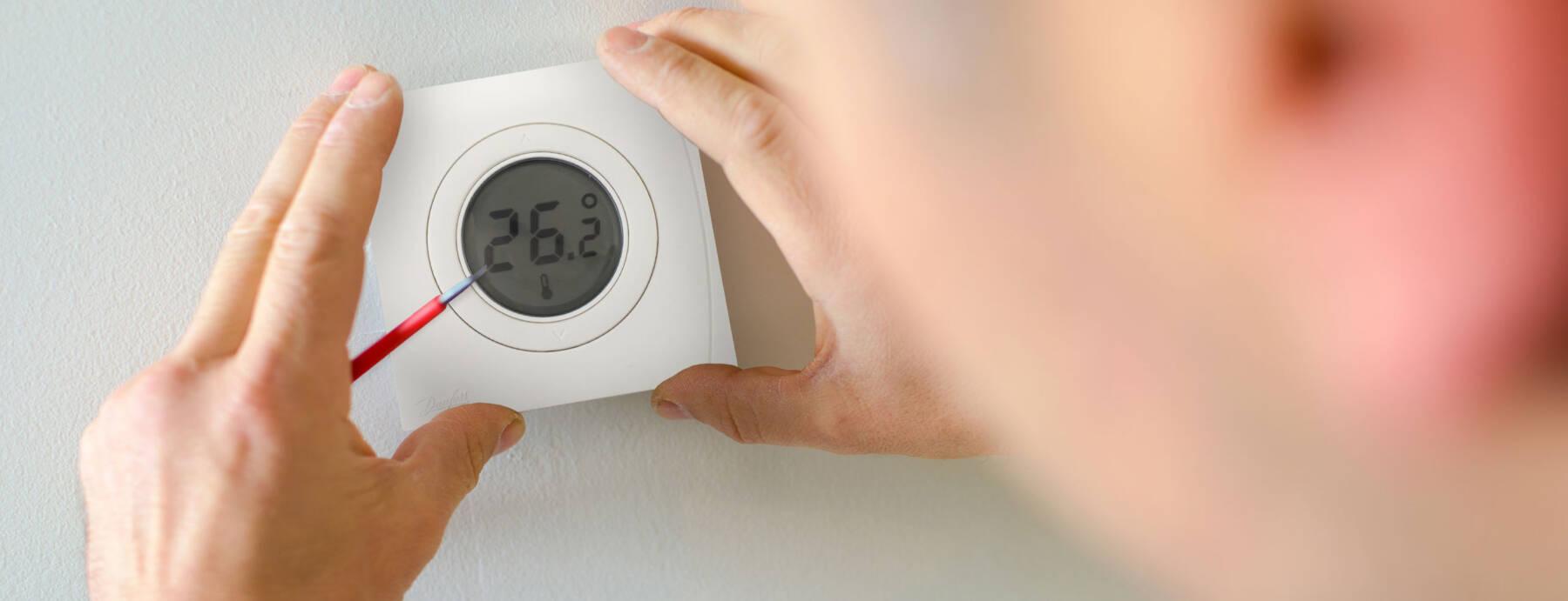 man installing the genius home thermostats SMART hub