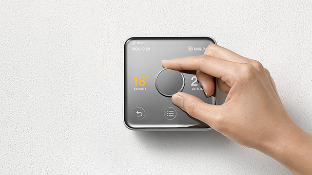 a hand operating a hive active heating 2 thermostat