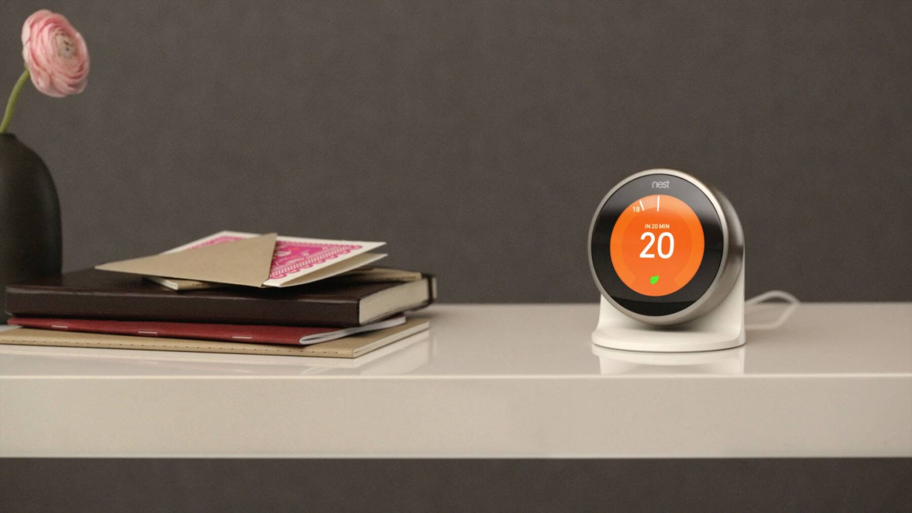 The nest learning thermostat on a desktop being used