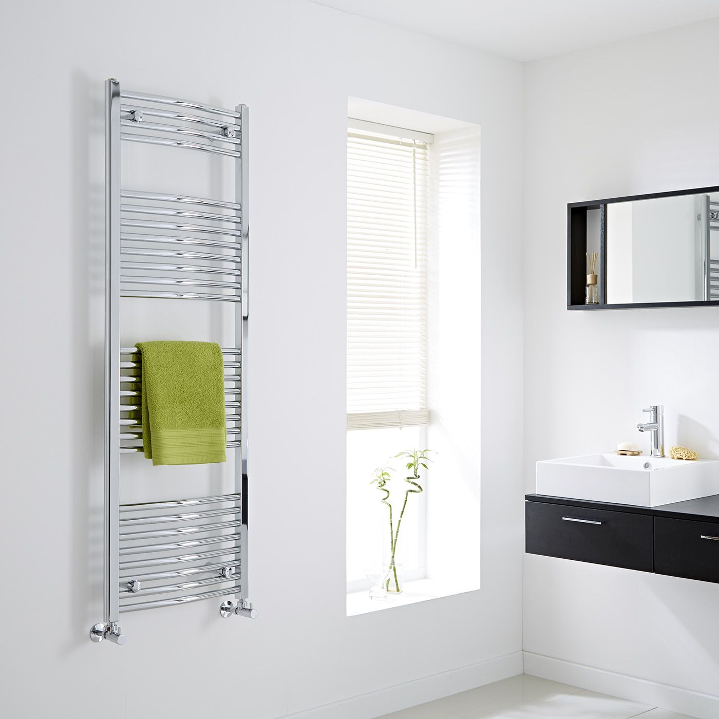 The Milano Ribble Curved heated Towel Rail gloriously gleaming on the wall of a bathroom