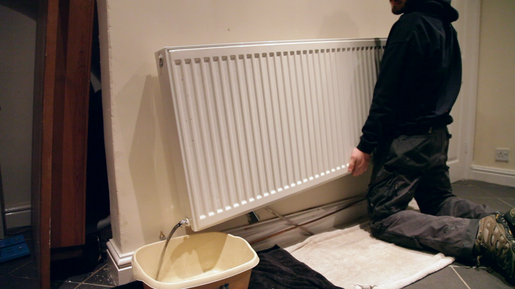 A man pouring away the contents of a radiator into a washing up bowl