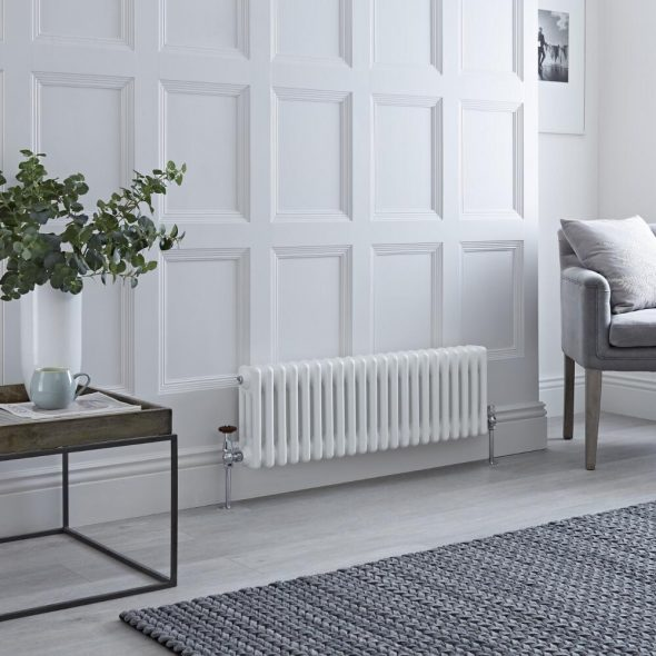 white radiator on white wall with grey furniture