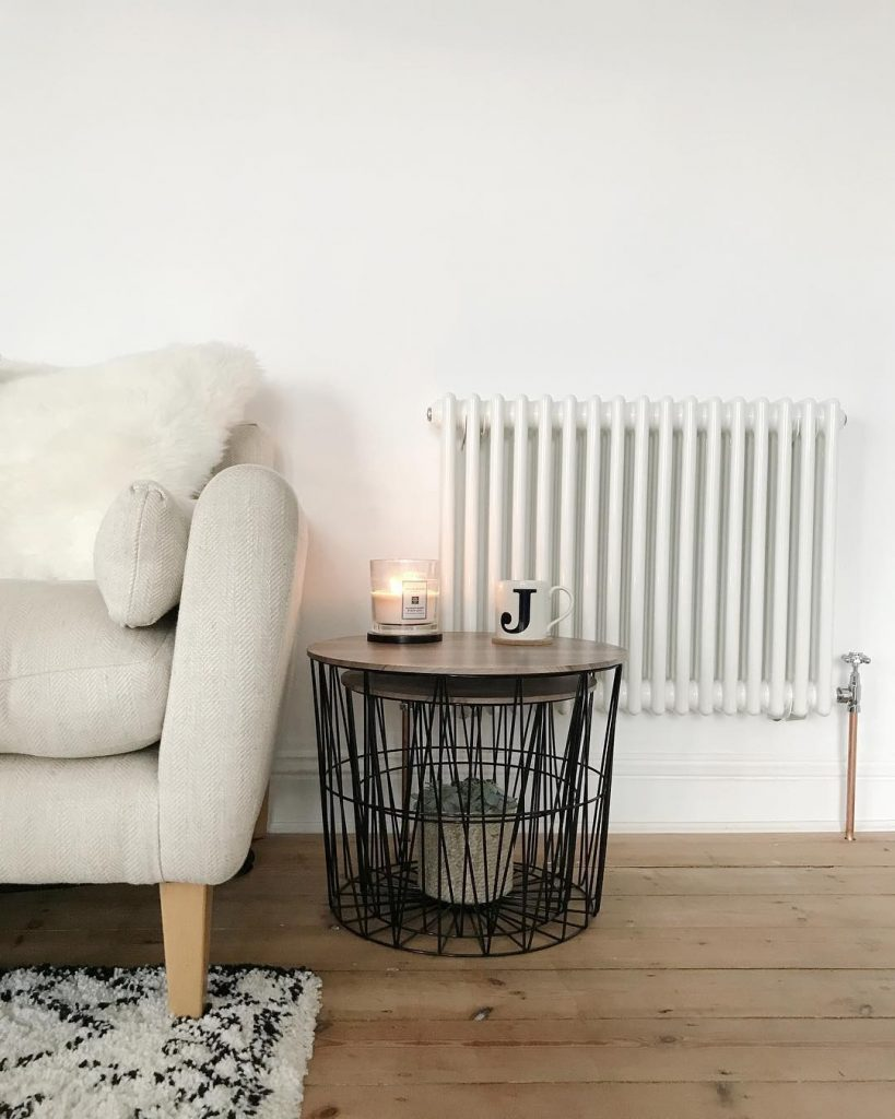 Scandinavian style chair, side table and white column radiator on a white wall