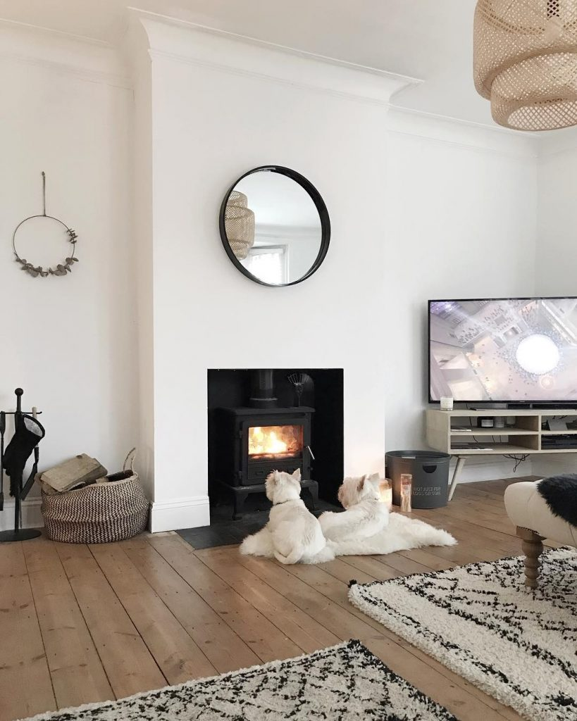 two westie dogs sat by the fire in a modern Scandinavian style home