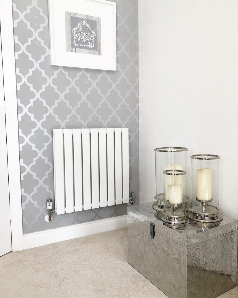 A white Milano Alpha designer radiator with thermostatic valves.