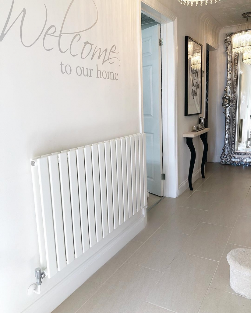 A white Milano Alpha designer radiator from BestHeating on a white wall.
