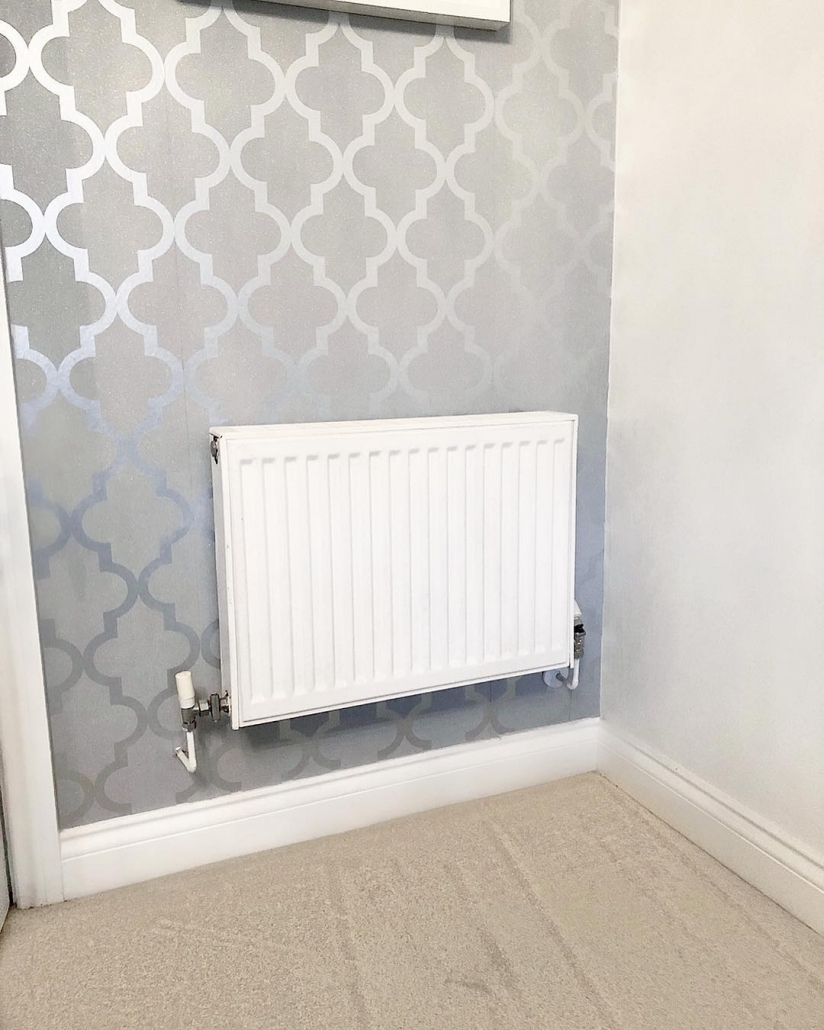 A white convector radiator on a grey wall.