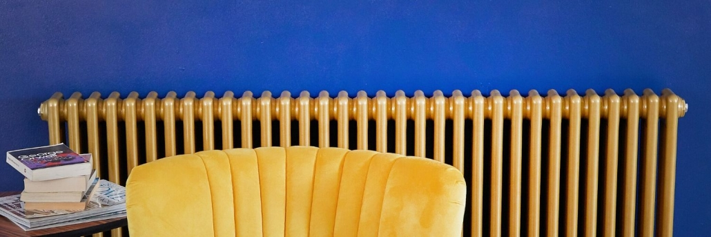 milano windsor gold radiator columns on a blue wall