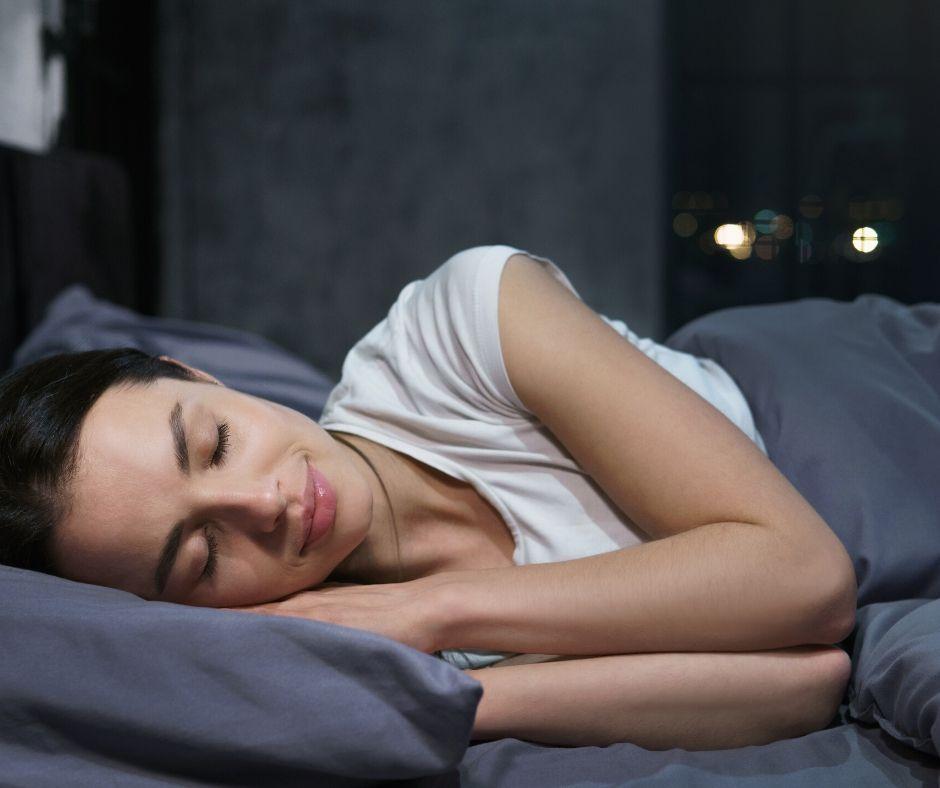 person asleep in a dark bedroom