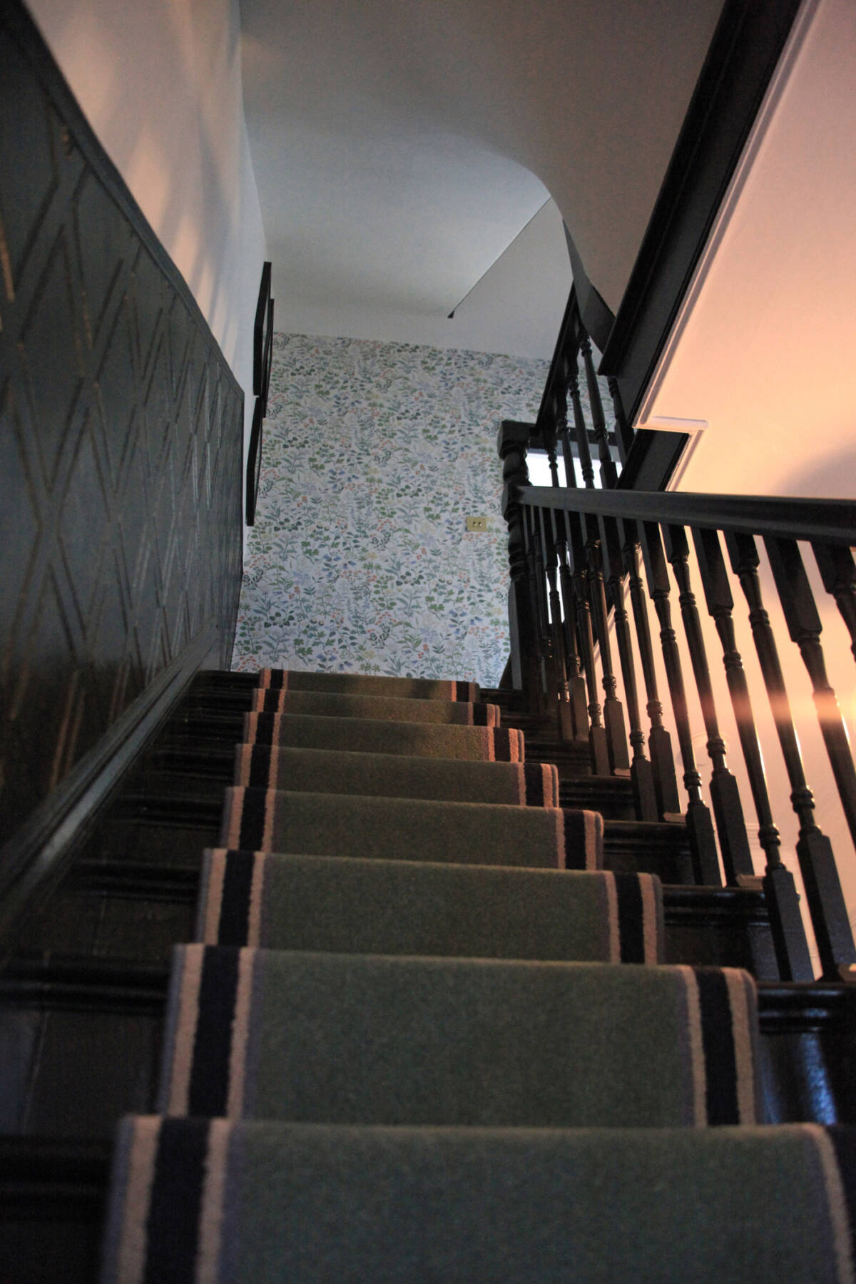 looking up a staircase with a runner carpet