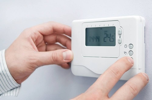 hands adjusting a thermostat on a wall