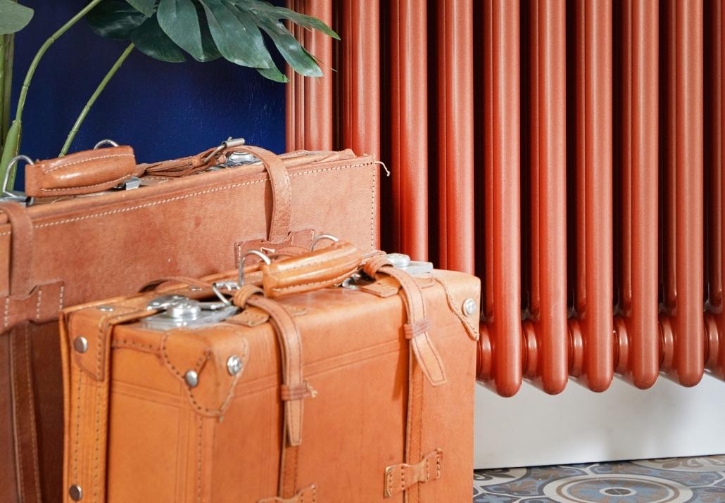 Milano Windsor copper vertical radaitor next to suitcases
