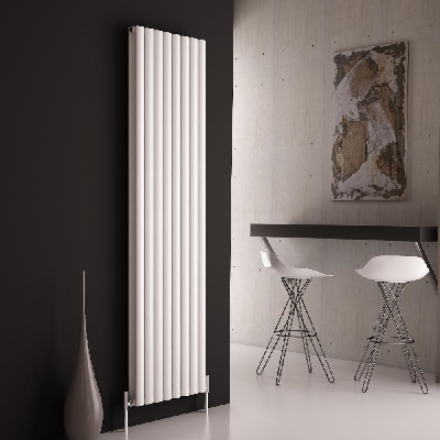 A tall white vertical radiator on a black wall
