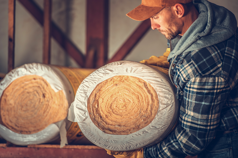 a workman holding a roll of insulation