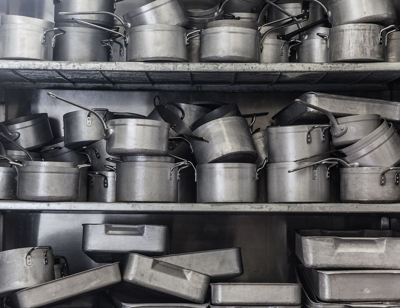 a shelving unit filled with pans of all shapes and sizes