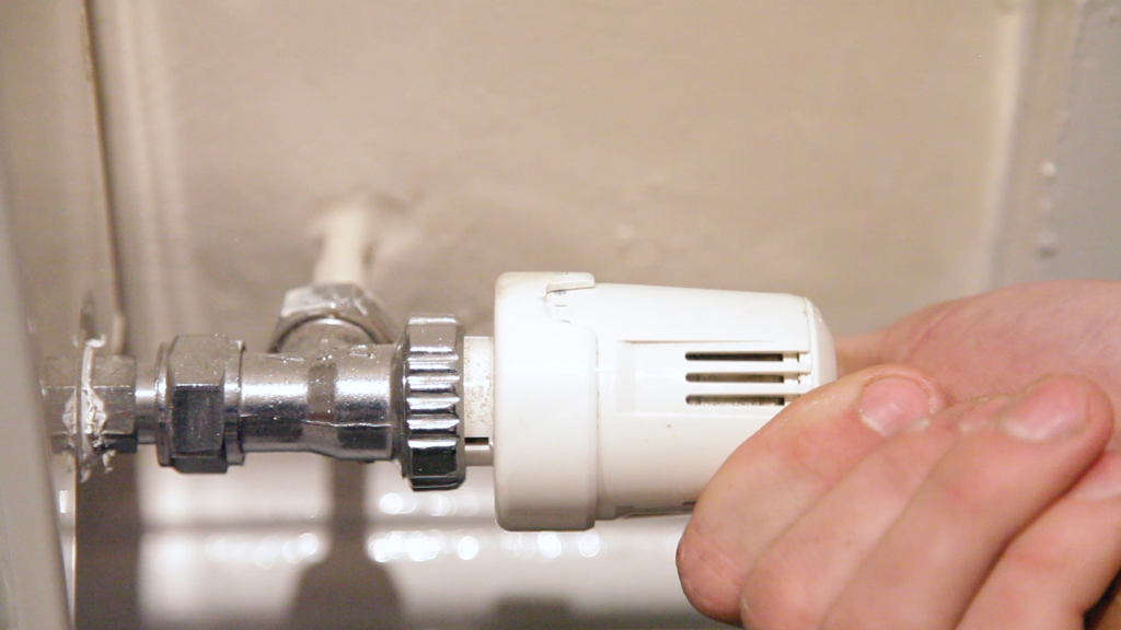 A hand closing a valve on a domestic radiator