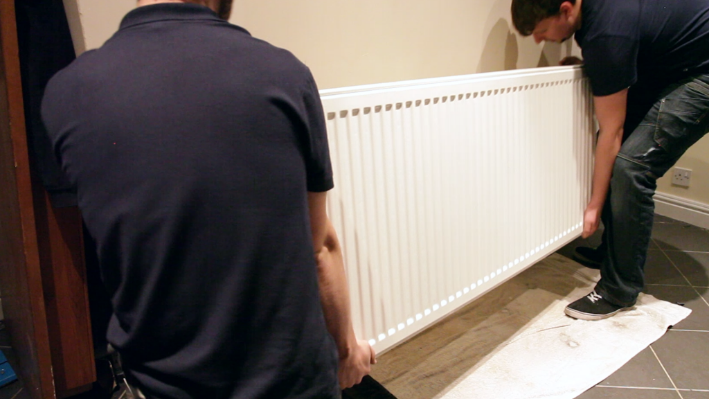 two men lifting a radiator off the wall