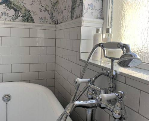 a traditional bath tap next to a bath