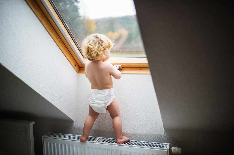 a small child climbing on a radiator
