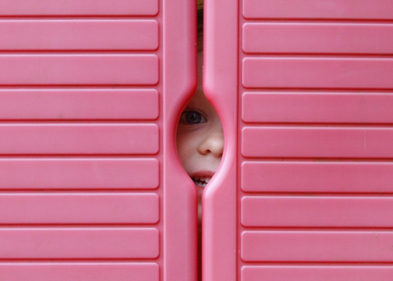a kid peeping through the dorr of a wendy house